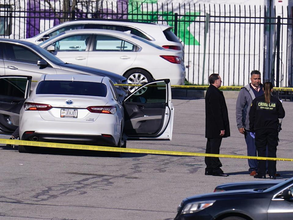 Authorities confer at the scene where multiple people were shot at the FedEx Ground facility early Friday morning, April 16, 2021, in Indianapolis. A gunman killed eight people and wounded several others before apparently taking his own life in a late-night attack at a FedEx facility near the Indianapolis airport, police said, in the latest in a spate of mass shootings in the United States after a relative lull during the pandemic. (AP Photo/Michael Conroy)