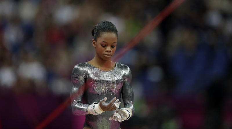 U.S. gymnast Gabrielle Douglas reacts after her performance on the uneven bars during the artistic gymnastics women's apparatus finals at the 2012 Summer Olympics, Monday, Aug. 6, 2012, in London. (AP Photo/Gregory Bull)