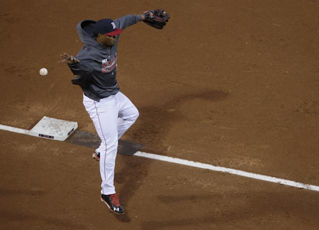 Boston Red Sox shortstop Xander Bogaerts reaches for a ball during a workout at Fenway Park Tuesday, Oct. 22, 2013, in Boston. The Red Sox are scheduled to host the St. Louis Cardinals in Game 1 of baseball's World Series on Wednesday. (AP Photo/Charles Krupa)