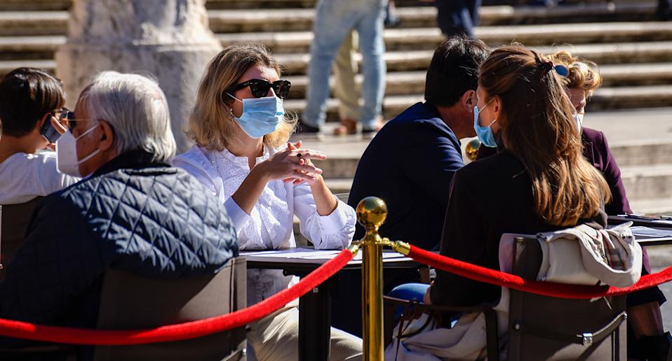 Women sit at a cafe table wearing masks in Italy. Source: AP