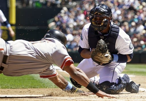 Seattle Mariners catcher Miguel Olivo, right, attempts to tag out San Francisco Giants baserunner Pablo Sandoval at home plate during the first inning of a baseball game at Safeco Field in Seattle, Sunday June 17, 2012. Sandoval scored on the play. (AP Photo/Stephen Brashear)