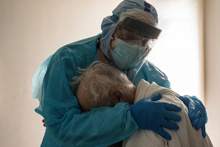 Dr. Joseph Varon hugs and comforts a patient in the COVID-19 intensive care unit (ICU) during Thanksgiving at the United Memorial Medical Center on November 26 in Houston, Texas.