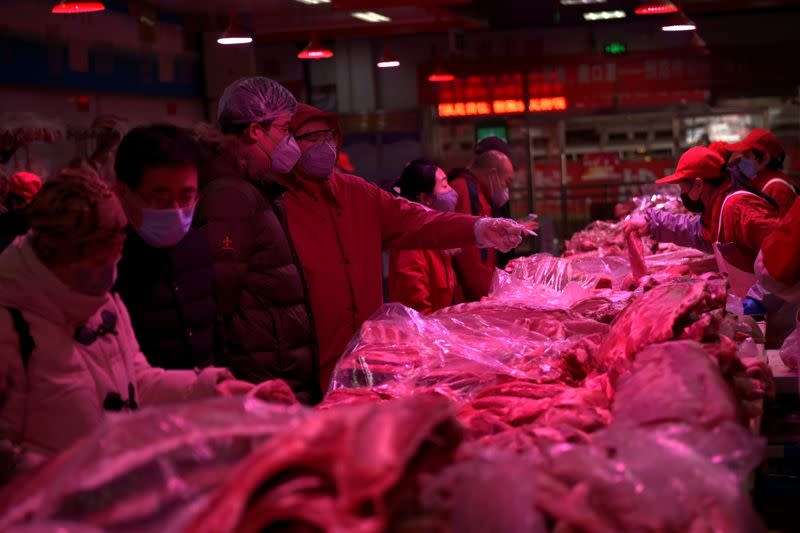 FILE PHOTO: Customers wearing face masks buy pork meat at a wholesale market for agricultural products, as the country is hit by an outbreak of the novel coronavirus, in Beijing