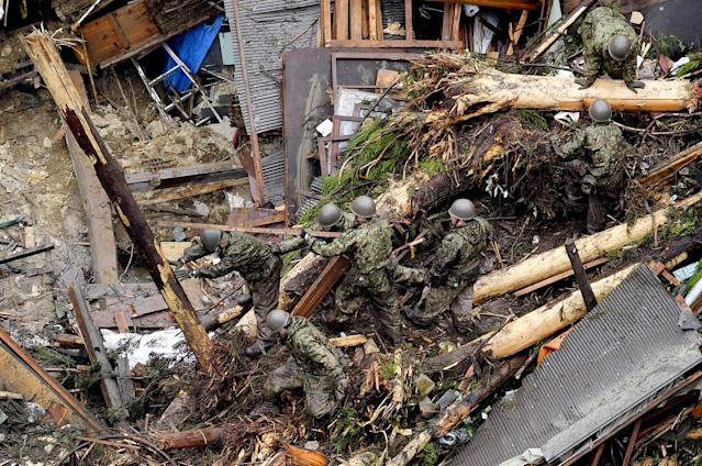 <p>Rescue workers from Japan's Self Defense Force search through debris piled over a house completely demolished by flooding caused by heavy rain in Toho, Fukuoka prefecture, southwestern Japan Thursday, July 6, 2017. Troops worked Thursday to rescue hundreds of people stranded by flooding in southern Japan. (Photo: Nozomu Endo/Kyodo News via AP) </p>