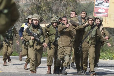 Israeli soldiers carry a wounded comrade on a stretcher near Israel's border with Lebanon January 28, 2015. REUTERS/JINIPIX