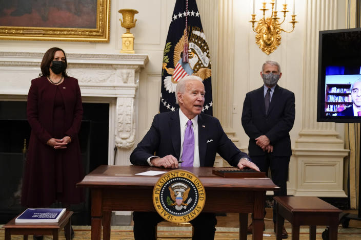 President Joe Biden responds to a reporters question after signing executive orders in the State Dinning Room of the White House, Thursday, Jan. 21, 2021, in Washington. Vice President Kamala Harris, left, and Dr. Anthony Fauci, director of the National Institute of Allergy and Infectious Diseases, right, look on. (AP Photo/Alex Brandon)