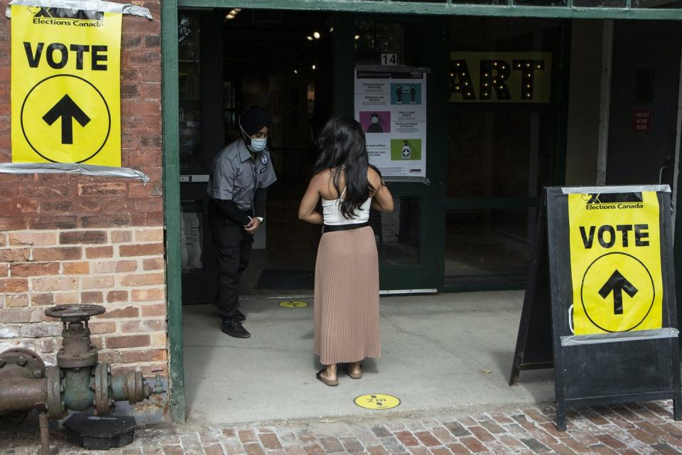 A woman lines up outside a building to vote with yellow vote signs on either side of her.