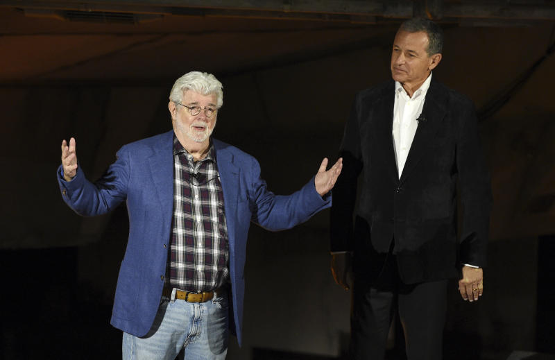 """Star Wars"" film franchise creator George Lucas, left, addresses the crowd as Walt Disney Co. Chairman and CEO Bob Iger looks on during a dedication ceremony for the Star Wars: Galaxy's Edge attraction at Disneyland Park, Wednesday, May 29, 2019, in Anaheim, Calif. (Photo by Chris Pizzello/Invision/AP)"