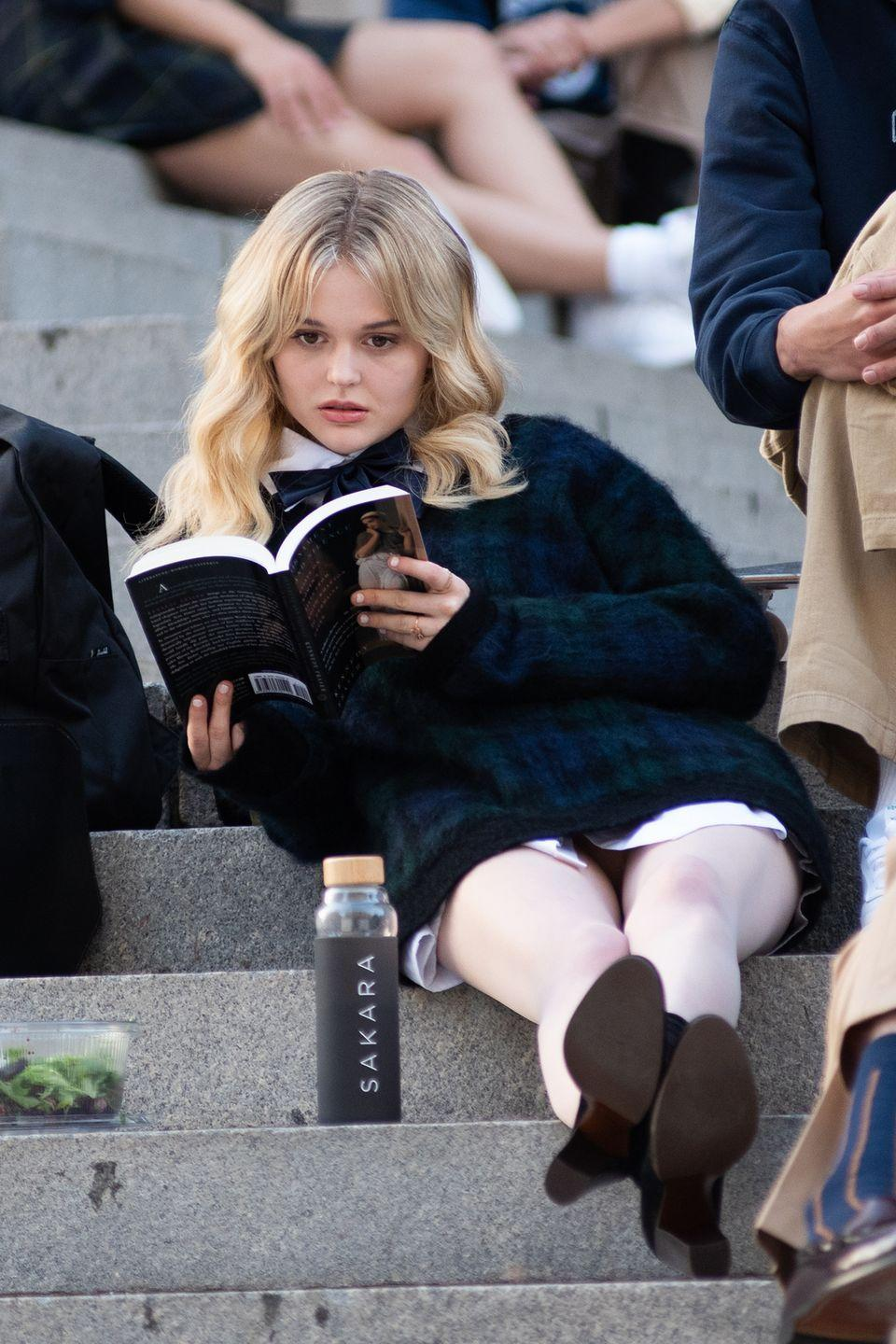 <p>Emily Alyn Lind reads on the steps of The Met. Is that a Sakara lunch we see?</p>
