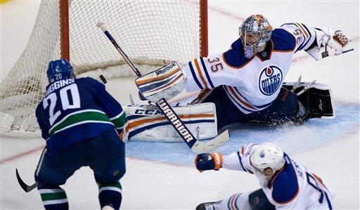 Vancouver Canucks' Chris Higgins, left, scores against Edmonton Oilers' goalie Nikolai Khabibulin, of Russia, during the third period of an NHL hockey game Thursday, April 4, 2013, in Vancouver, British Columbia. (AP Photo/The Canadian Press, Darryl Dyck)