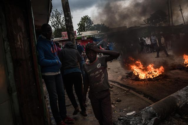 <p>People walk by a burning roadblock lit protest for opposition presidential candidate Raila Odinga, in the Kibera slum, on Oct. 25, 2017 in Nairobi, Kenya. (Photo: Andrew Renneisen/Getty Images) </p>