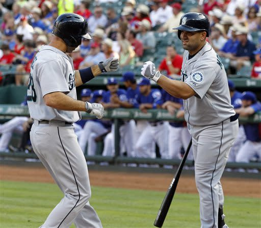Seattle Mariners left fielder Raul Ibanez, left, is congratulated at home plate by teammate Kendrys Morales, after hitting a solo home run during the first inning of a baseball game Tuesday, July 2, 2013, in Arlington, Texas. Morales, the next batter up, then hit another home run. (AP Photo/John F. Rhodes)