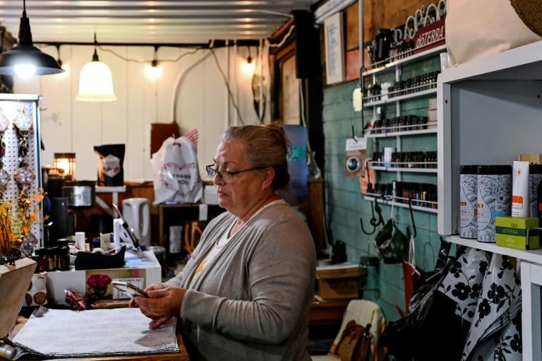 Yvonne Wallech looks at her mobile phone while tending to her gift shop in Green Bank, West Virginia (AFP/ROBERTO SCHMIDT)