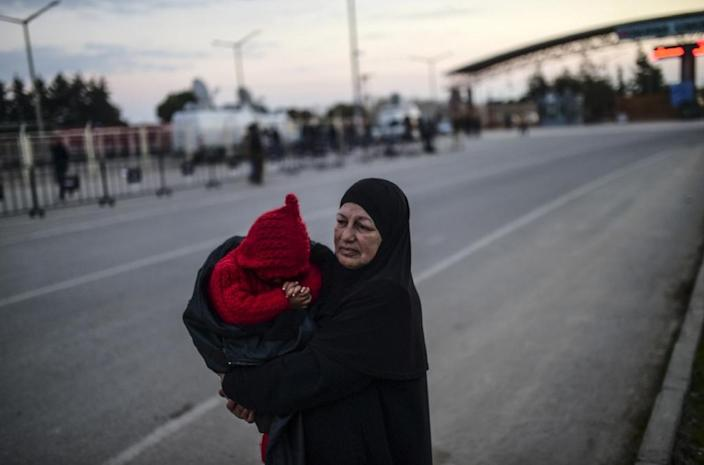 Syrian refugee Hatice Henidil hugs her grandson while waiting for his parents still stuck on the Syrian side of the border, in front of the Oncupinar crossing gate, near the town of Kilis, in south-central Turkey on February 10, 2016 (AFP Photo/Bulent Kilic)