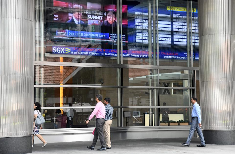 People walk outside the SGX stock exchange building in Singapore on June 13, 2018. (Photo by ROSLAN RAHMAN / AFP)        (Photo credit should read ROSLAN RAHMAN/AFP/Getty Images)