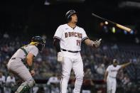 Arizona Diamondbacks' Asdrubal Cabrera (14) flips the bat in the air after striking out as Oakland Athletics catcher Sean Murphy checks the base runners during the first inning of a baseball game Monday, April 12, 2021, in Phoenix. (AP Photo/Ross D. Franklin)