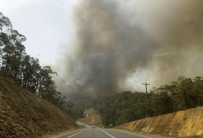 Smoke from a fire at Batemans Bay, Australia, billows into the air, Saturday, Jan. 4, 2020. Australia's prime minister called up about 3,000 reservists as the threat of wildfires escalated in at least three states on Saturday, while strong winds and high temperatures were forecast to bring flames to populated areas including the suburbs of Sydney. (AP Photo/Rick Rycroft)