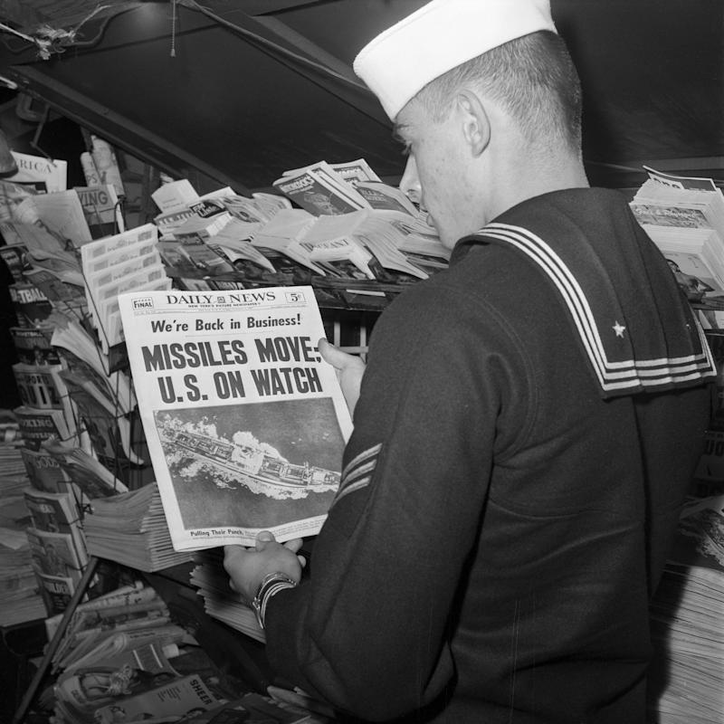 U.S. sailor reads the front page of the New York Daily News at a newsstand on November 9, 1962. (Getty Images)