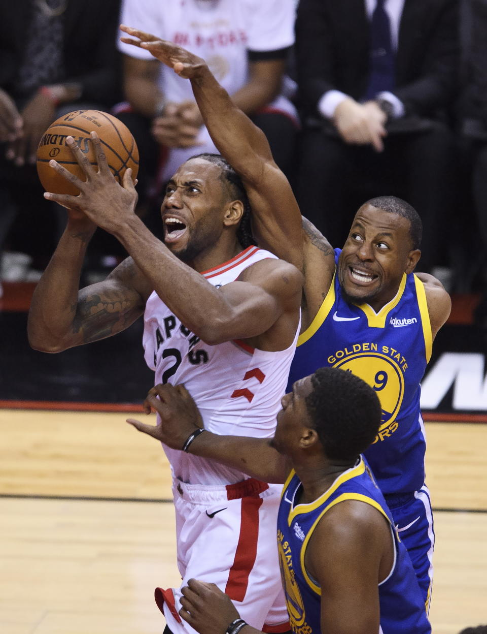 Toronto Raptors forward Kawhi Leonard (2) drives to the net against Golden State Warriors guard Andre Iguodala (9) during the first half of Game 1 of basketball's NBA Finals, Thursday, May 30, 2019, in Toronto. (Nathan Denette/The Canadian Press via AP)