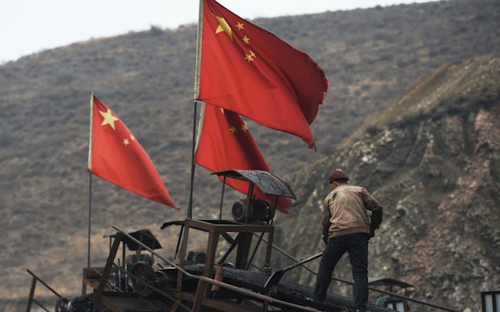 Chinese flags next to a worker clearing a conveyer belt - GREG BAKER/AFP