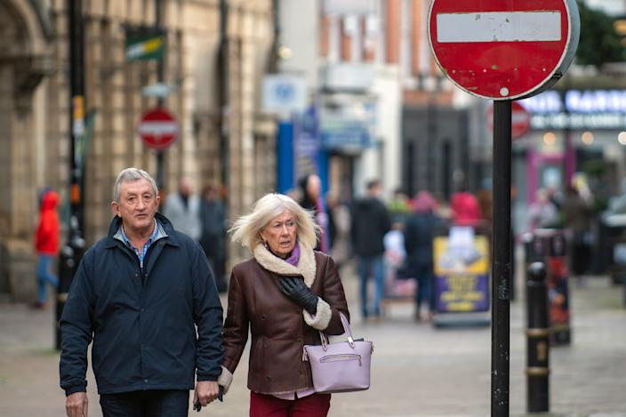 People walk along Fish Street in Northampton, as further changes to England's tier system are expected to be announced, just days after millions of people came under harsher coronavirus restrictions on Boxing Day.