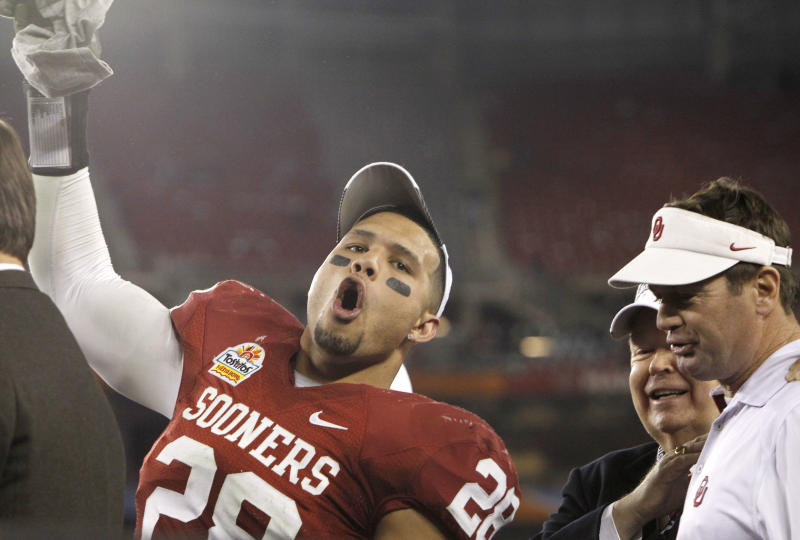 Oklahoma's Travis Lewis (28) celebrates as head coach Bob Stoops, right, and university president David L. Boren look on after a Fiesta Bowl NCAA college football game victory against Connecticut Saturday, Jan. 1, 2011, in Glendale, Ariz.  Oklahoma defeated Connecticut 48-20. (AP Photo/Ross D. Franklin)