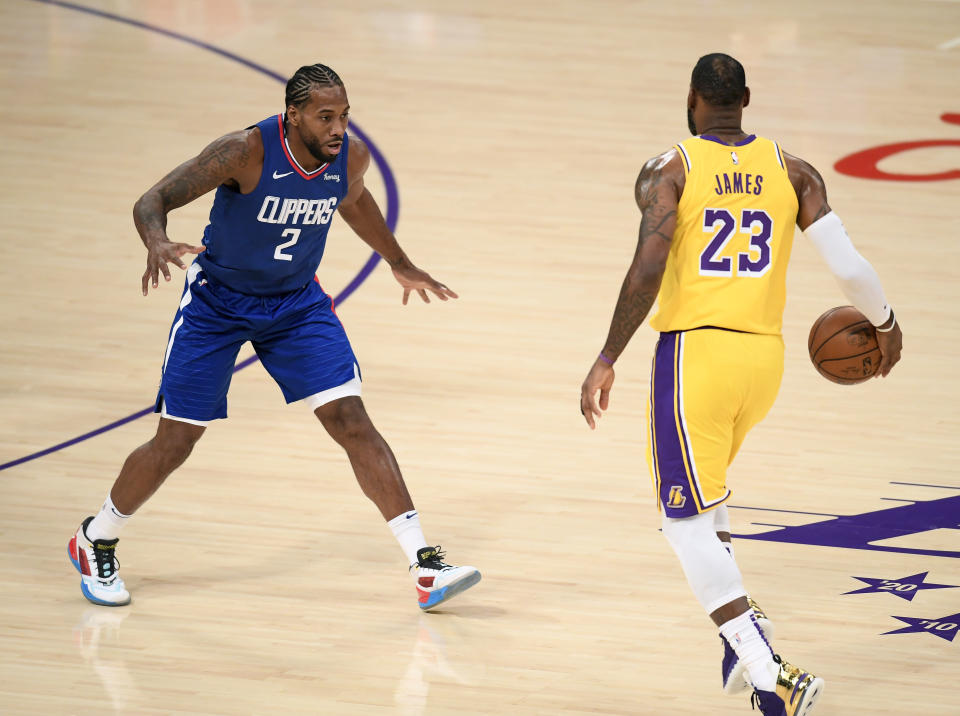 Kawhi Leonard #2 of the LA Clippers guards LeBron James #23 of the Los Angeles Lakers during the season opening game at Staples Center on December 22, 2020 in Los Angeles, California.