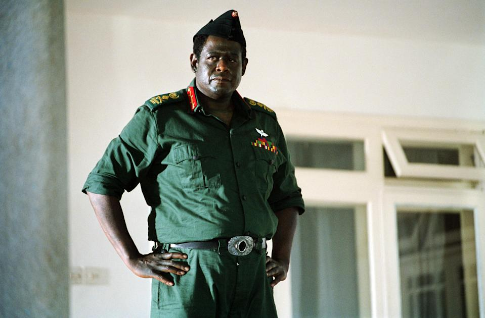 Forest Whitaker stands dressed as Idi Amin
