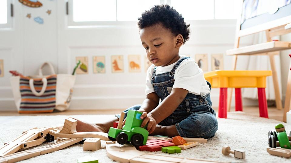 Cute little boy playing with a railroad train toy.