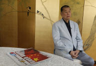 Hong Kong media tycoon Jimmy Lai pauses next to a copy of Apple Daily's July 1, 2020, edition during an interview Hong Kong Wednesday, July 1, 2020. A newspaper that has advocated for greater democracy in Hong Kong came under further pressure Thursday, June 17, 2021, with the arrests of three top editors and two senior executives.(AP Photo/Vincent Yu, File)
