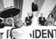 ADDS IDENTITY OF EDWARD'S FIRST WIFE - FILE - In this Oct. 22, 1980 file photo, an umbrella-carrying member of a Dixieland jazz band tips his hat to President Jimmy Carter as former Louisiana Gov. Edwin Edwards and his first wife, Elaine Schwartzenburg Edwards, applaud in a New Orleans hotel ballroom, where Carter spoke. Edwards, the high-living four-term governor whose three-decade dominance of Louisiana politics was all but overshadowed by scandal and an eight-year federal prison stretch, died Monday, July 12, 2021, of respiratory problems. He was 93. (AP Photo/John Duricka, File)