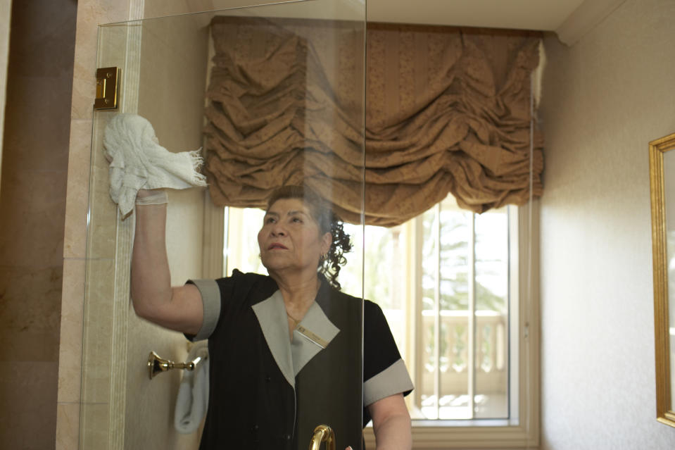 Maid clearing glass door in hotel bathroom