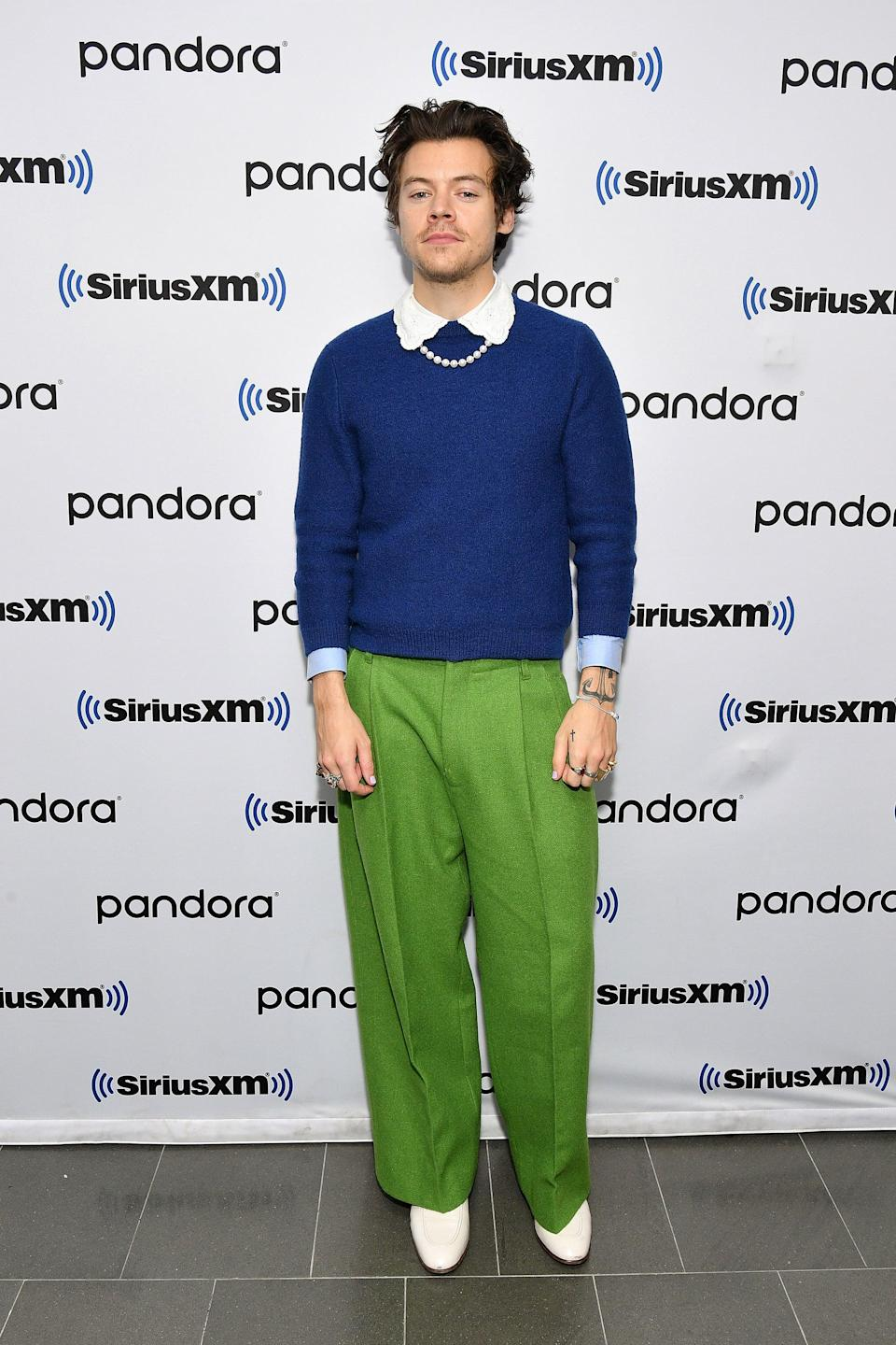 <p>We have no choice but to stan this colorblocking king! While visiting the SiriusXM Studios in New York City in March 2020, Harry layered a classic royal blue sweater over a scallop-collared shirt and finished the look with green trousers, a pearl necklace, and white loafers.</p>
