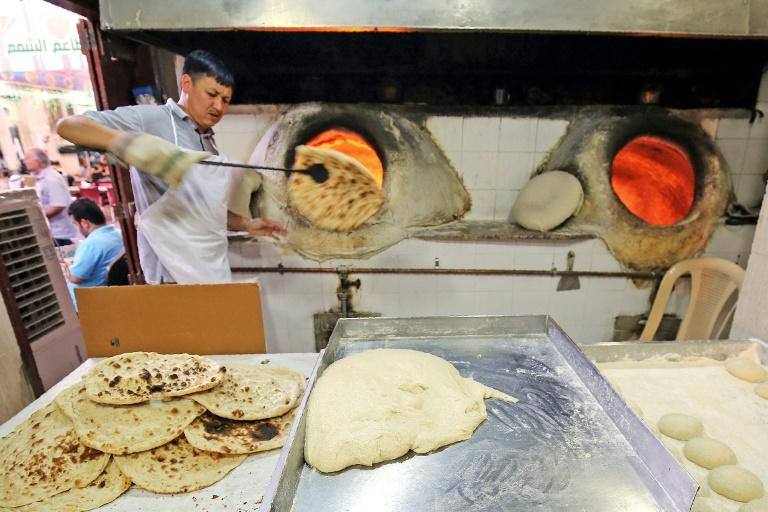 A baker bakes Iranian bread - known as taftoon - in Kuwait City in traditional clay ovens. Once ready he uses a long stick to reach in and pull out a steaming round loaf (AFP Photo/Yasser Al-Zayyat)