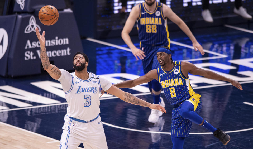 Los Angeles Lakers forward Anthony Davis (3) works to regain control of the ball as Indiana Pacers forward Justin Holiday (8) defends during the second half of an NBA basketball game in Indianapolis, Saturday, May 15, 2021. (AP Photo/Doug McSchooler)