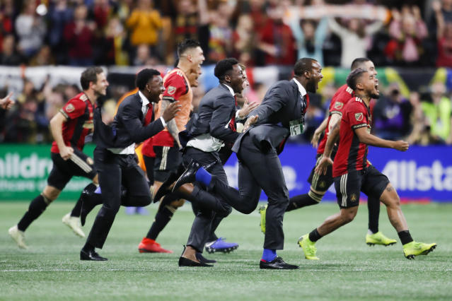 Members of Atlanta United charge the field as the game concludes in the MLS Cup championship soccer game against the Portland Timbers, Saturday, Dec. 8, 2018, in Atlanta. Atlanta United won 2-0. (AP Photo/Todd Kirkland)