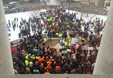 Workers gather outside the State Capitol building in Madison