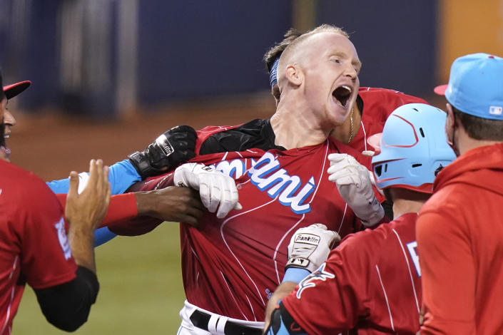 Miami Marlins' Garrett Cooper celebrates with teammates after hitting a walk-off two-run home run in the ninth inning of a baseball game against the New York Mets, Saturday, May 22, 2021, in Miami. The Marlins won 3-1. (AP Photo/Lynne Sladky)