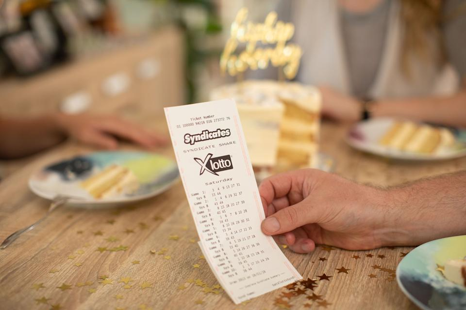 Lottery ticket with celebration cake and confetti in background. Source: The Lott
