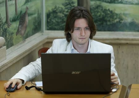 Raffaele Sollecito works at his computer before a news conference in Rome