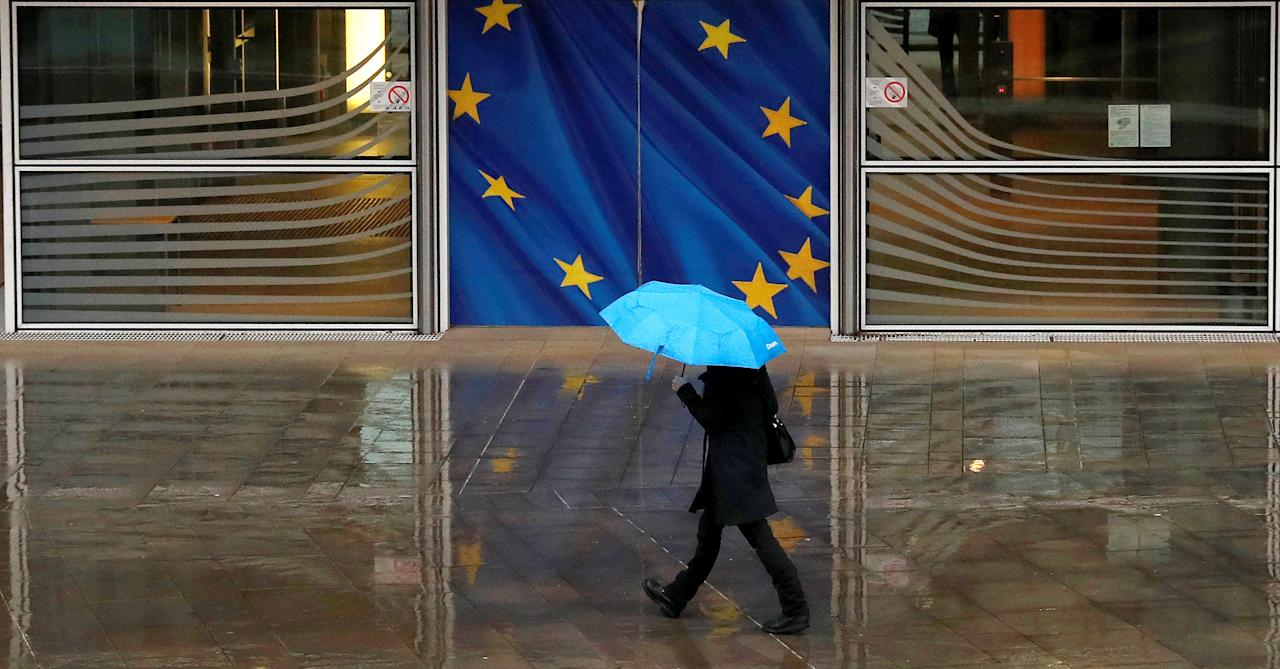A woman holds an umbrella as she walks past the flag of the European Union outside the European Commission in Brussels, Belgium, December 13, 2017. REUTERS/Phil Noble