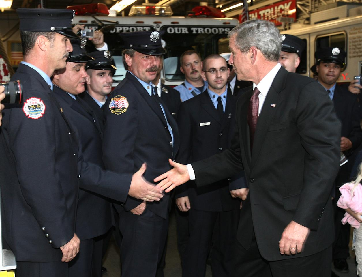 U.S. President George W. Bush greets New York firefighters from Ladder Company 10 located across the street from the World Trade Center site in New York September 10, 2006. Bush lay a wreath at Ground Zero before visiting a chapel for a memorial service. (REUTERS/Jason Reed)