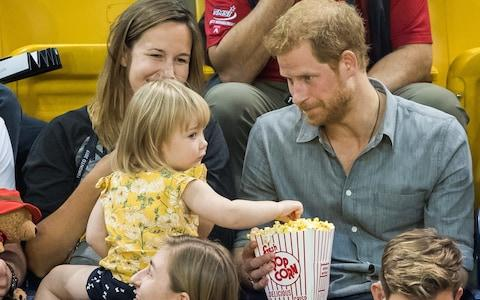 Butter wouldn't melt... as Emily is rumbled pinching Prince Harry's popcorn - Credit: Samir Hussein/WireImage