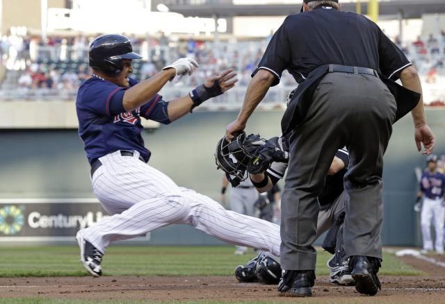 Minnesota Twins' Oswaldo Arcia, left, slides into the waiting tag by Chicago White Sox catcher Tyler Flowers in the first inning of a baseball game Tuesday, June 18, 2013 in Minneapolis. (AP Photo/Jim Mone)