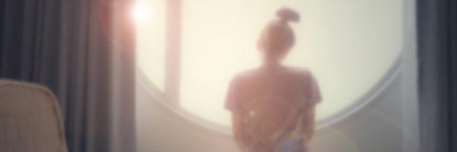 Abstract blurred of woman sitting looking through a window.