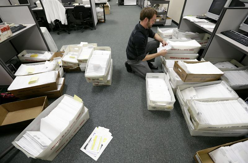 FILE - In this Sept. 26, 2012, file photo election clerk Karl Althaus sorts through boxes of absentee ballots at the Polk County Election Office in Des Moines, Iowa. Five weeks to Election Day, President Barack Obama is within reach of the requisite 270 Electoral College votes needed to win a second term according to an Associated Press analysis. Mitt Romney can still prevail in the race to amass the necessary votes, but his path to victory has become much narrower. To overtake Obama, the Republican challenger would need to quickly gain the upper hand in nearly all of the nine states where he and Obama are competing the hardest. (AP Photo/Charlie Neibergall, File)