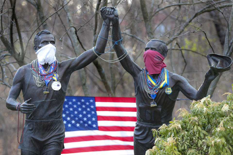 The Young at Heart Johnny Kelley statue by Rich Muno on Commonwealth Avenue wears a mask, Mardi Gras beads and Boston Marathon medals. (Matthew J. Lee/The Boston Globe via Getty Images)