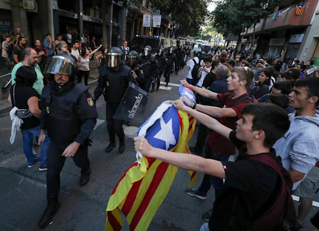 <p>Protestors wave Esteladas (Catalan separatist flags) at a line of Spanish national police who surrounded the leftist Popular Unity Candidacy (CUP) party headquarters in Barcelona, Spain, Sept. 20, 2017. (Photo: Albert Gea/Reuters) </p>