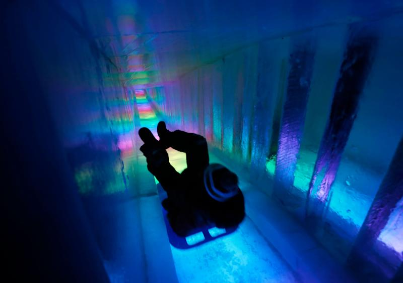 A man zooms down a 97-foot ice slide at Ice Castles in North Woodstock, N.H. (Photo: Robert F. Bukaty/AP)