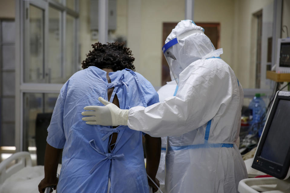 A medical worker attends to a coronavirus patient in the intensive care unit of an isolation and treatment center for those with COVID-19 in Machakos, south of the capital Nairobi, in Kenya Tuesday, Nov. 3, 2020. As Africa is poised to surpass 2 million confirmed coronavirus cases it is Kenya's turn to worry the continent with a second surge in infections well under way. (AP Photo/Brian Inganga)